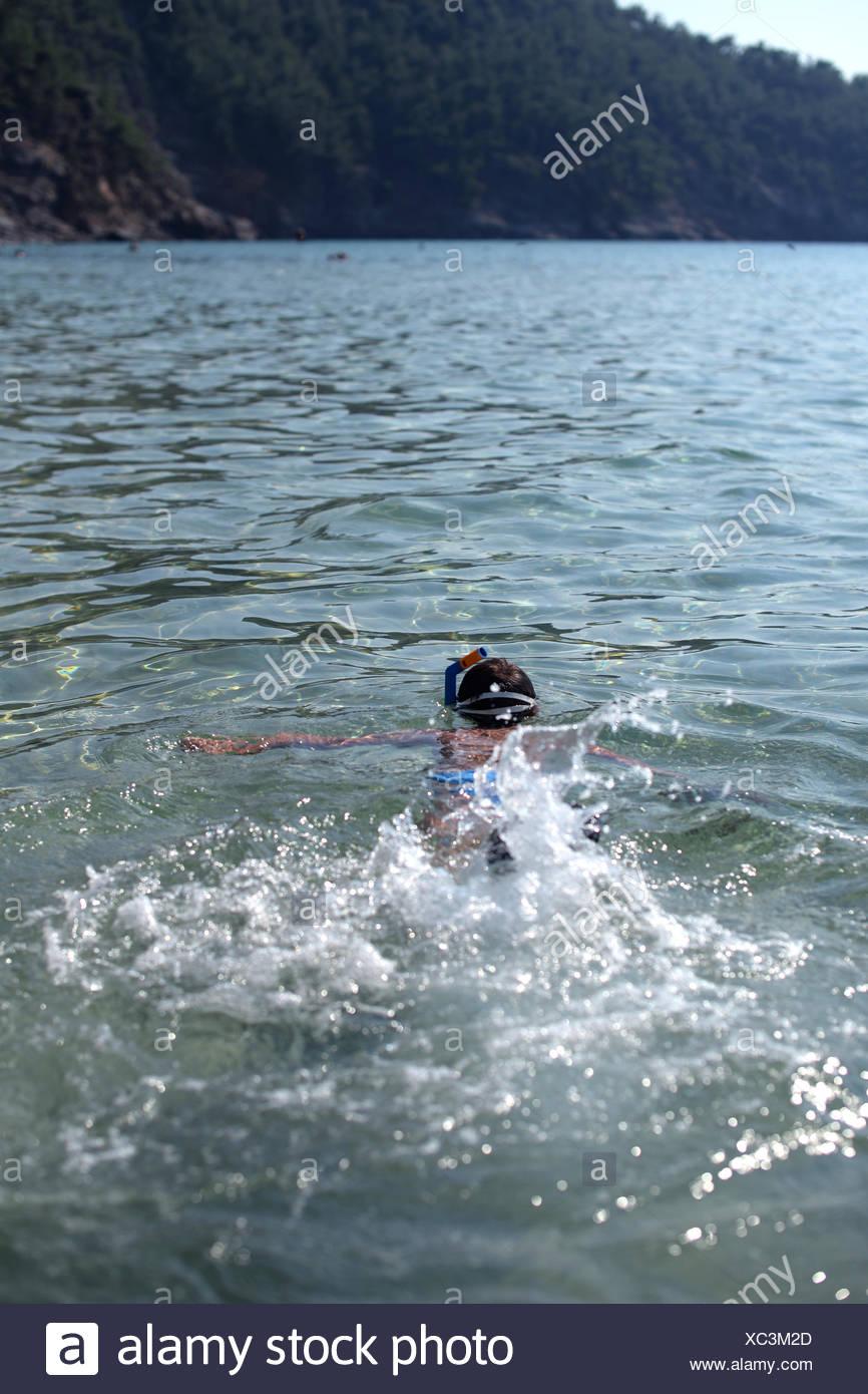 Boy splashing sur la mer dans le port d'un masque et tuba, Thassos, Grèce Photo Stock
