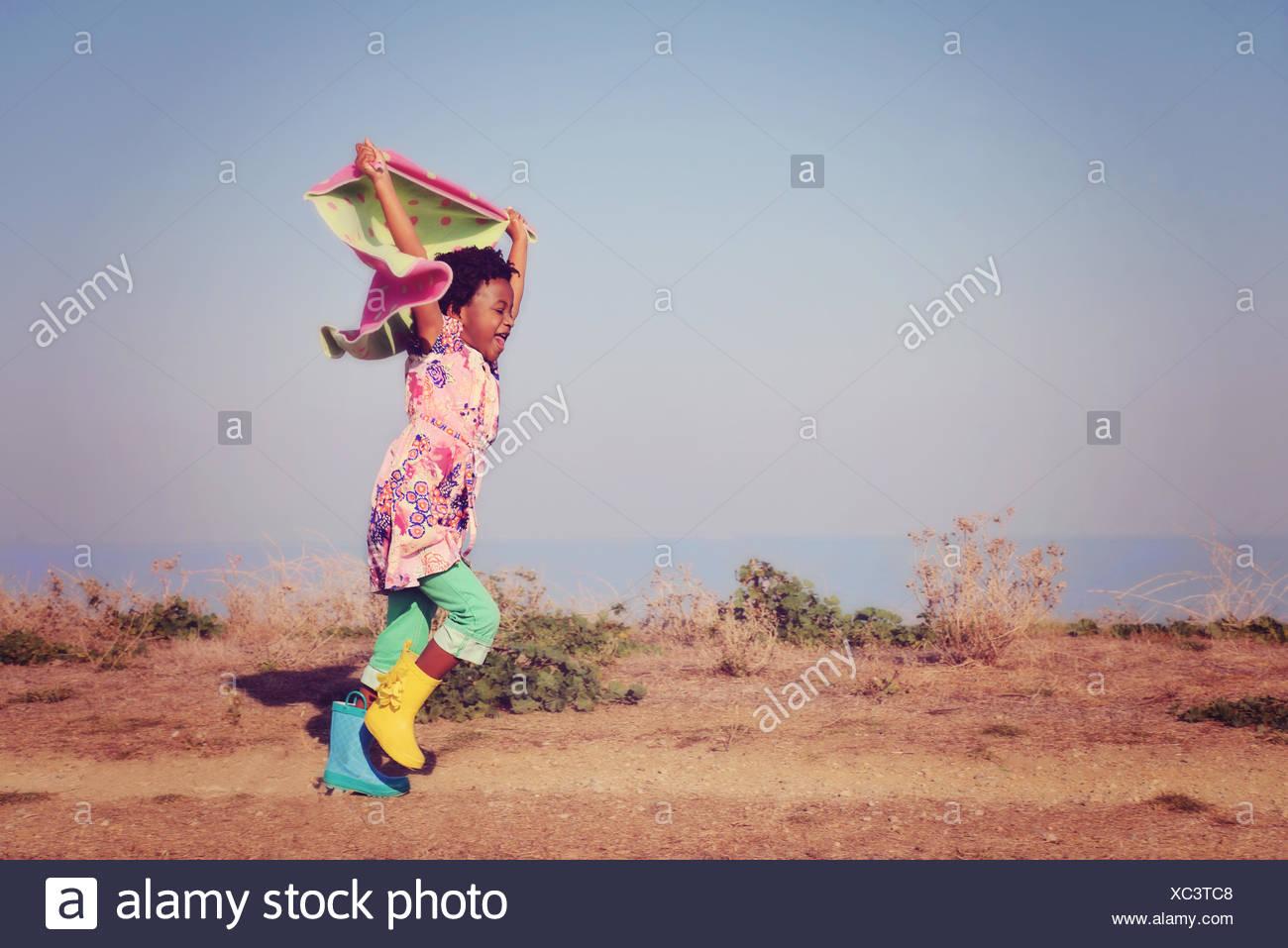 Foulard fille courir tenant au-dessus de sa tête Photo Stock