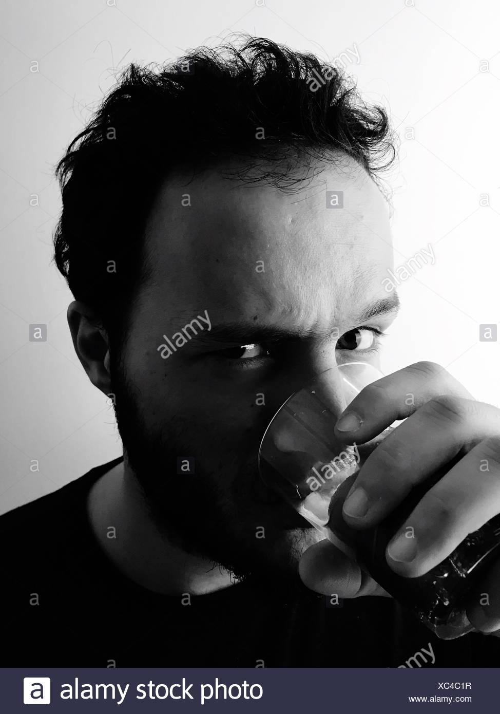 Portrait d'un homme ayant un verre à la maison Photo Stock