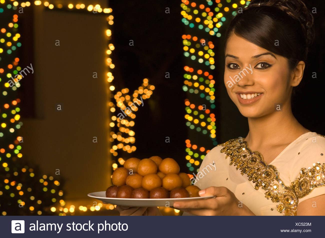 Woman holding bonbons dans une assiette et smiling Banque D'Images