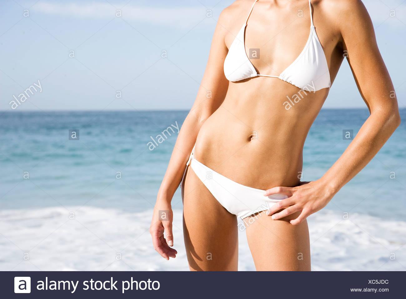 Une jeune femme sur la plage en bikini Photo Stock