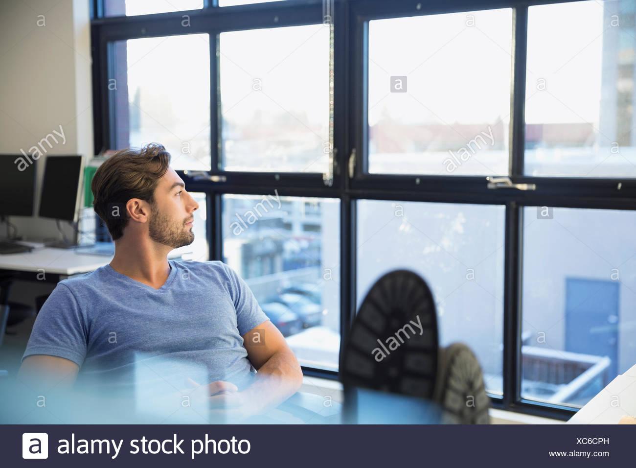 Pensive businessman avec les pieds jusqu'à la fenêtre de sortie Photo Stock