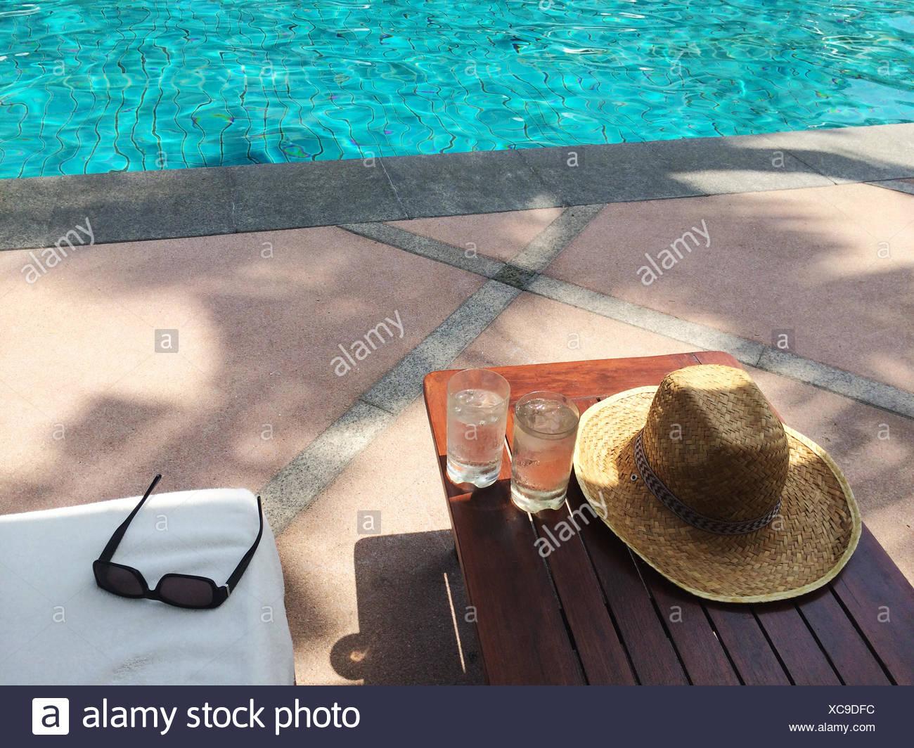 Chapeau, lunettes de soleil de paille et deux verres d'eau par piscine Photo Stock