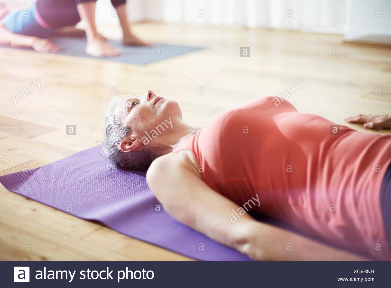 Young woman lying on retour en classe de pilates Photo Stock