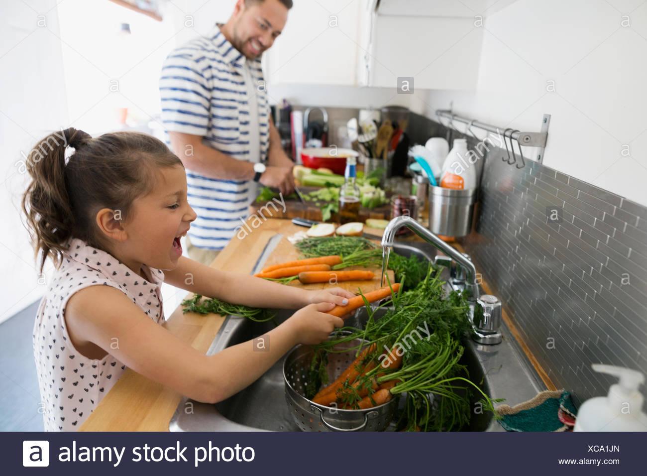 Père et fille de cuisson des carottes à laver évier de cuisine Photo Stock