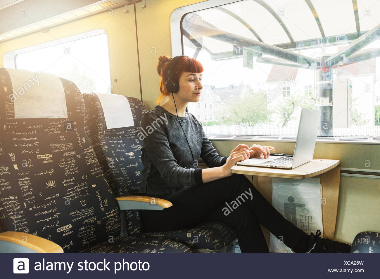 Woman using laptop on train Photo Stock