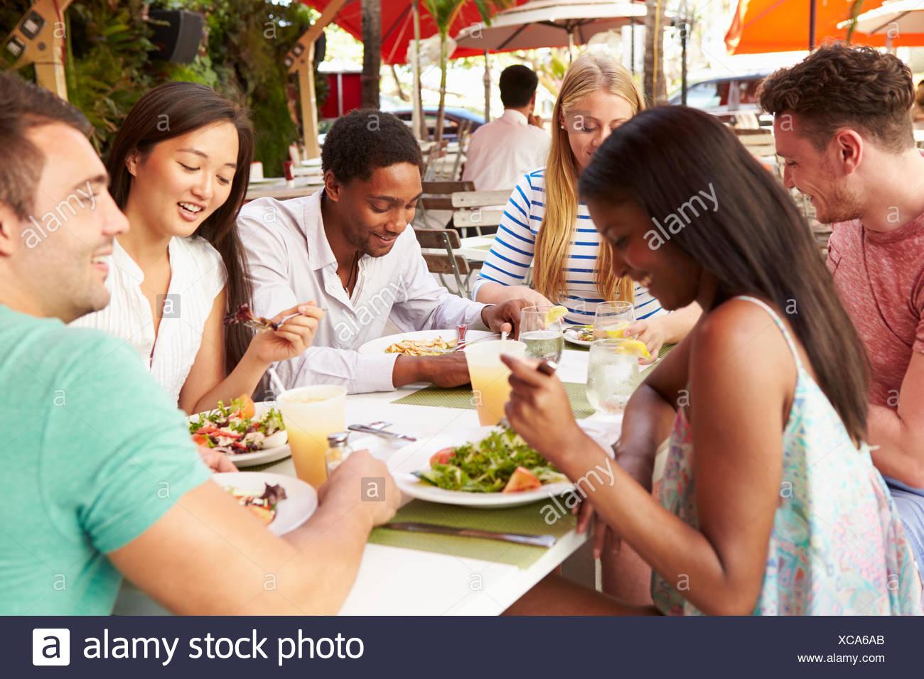Groupe d'amis appréciant le déjeuner en restaurant en plein air Photo Stock