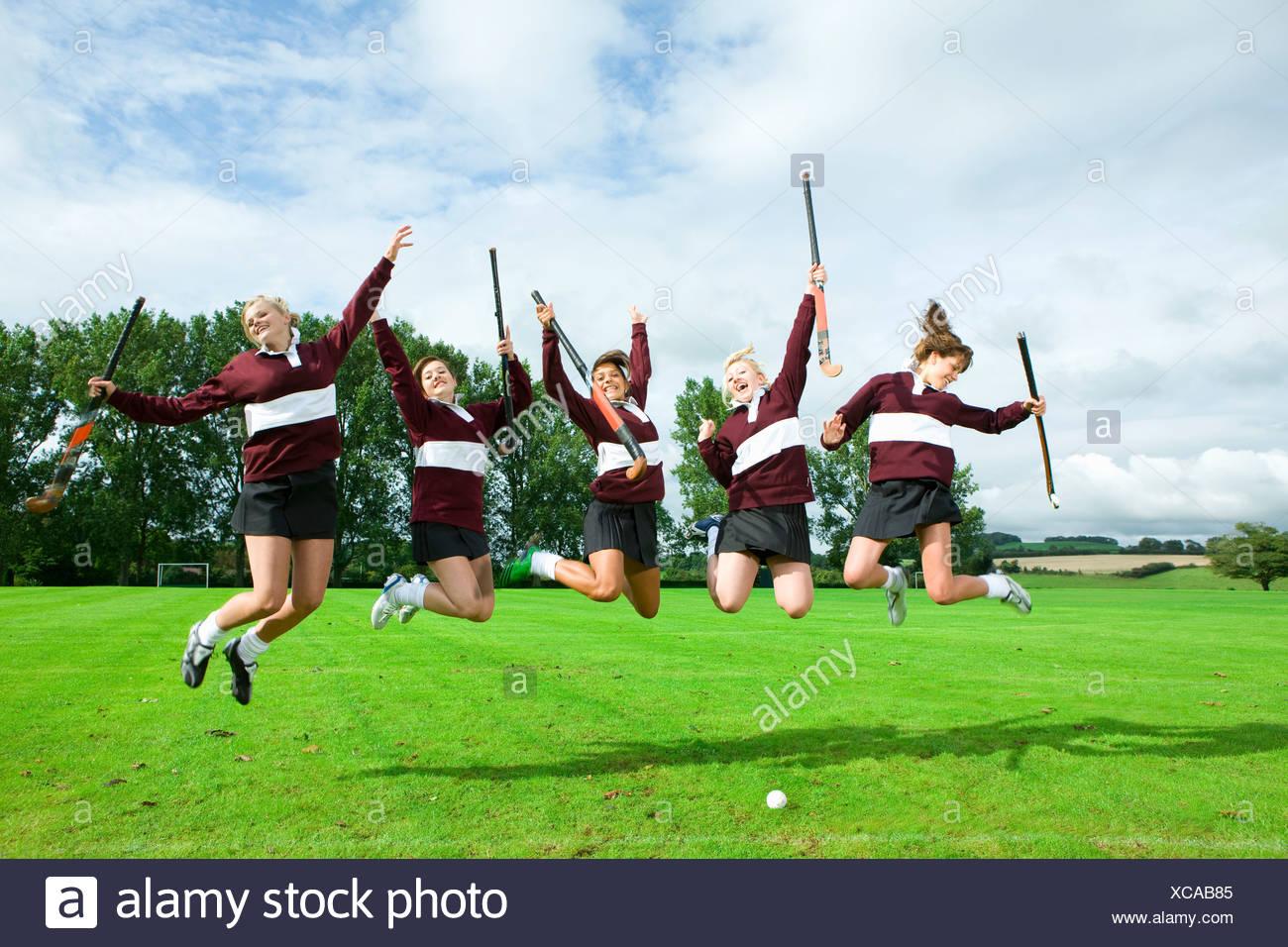 L'équipe de hockey adolescente sautant sur terrain Photo Stock