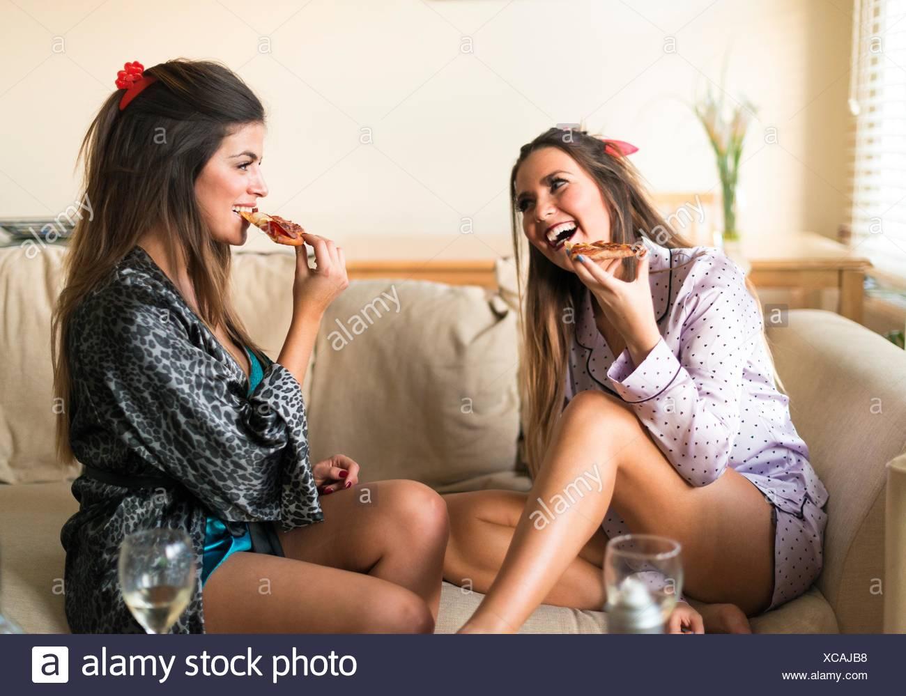 Deux jeunes femmes ayant des filles dans la nuit, assis sur le canapé, manger et rire Photo Stock