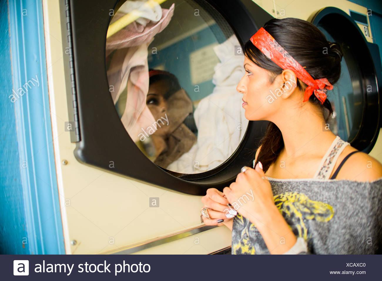 Jeune femme dans la laverie automatique, machine à laver regarder Photo Stock