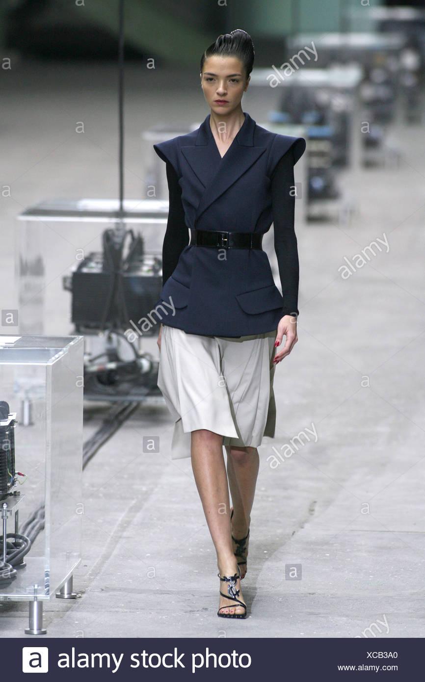 Modèle Mariacarla Boscono italien portant veste noire sans manches  ceinturée envelopper les épaules en avant, porté par-dessus noir à manches  longues e4b94ec0761