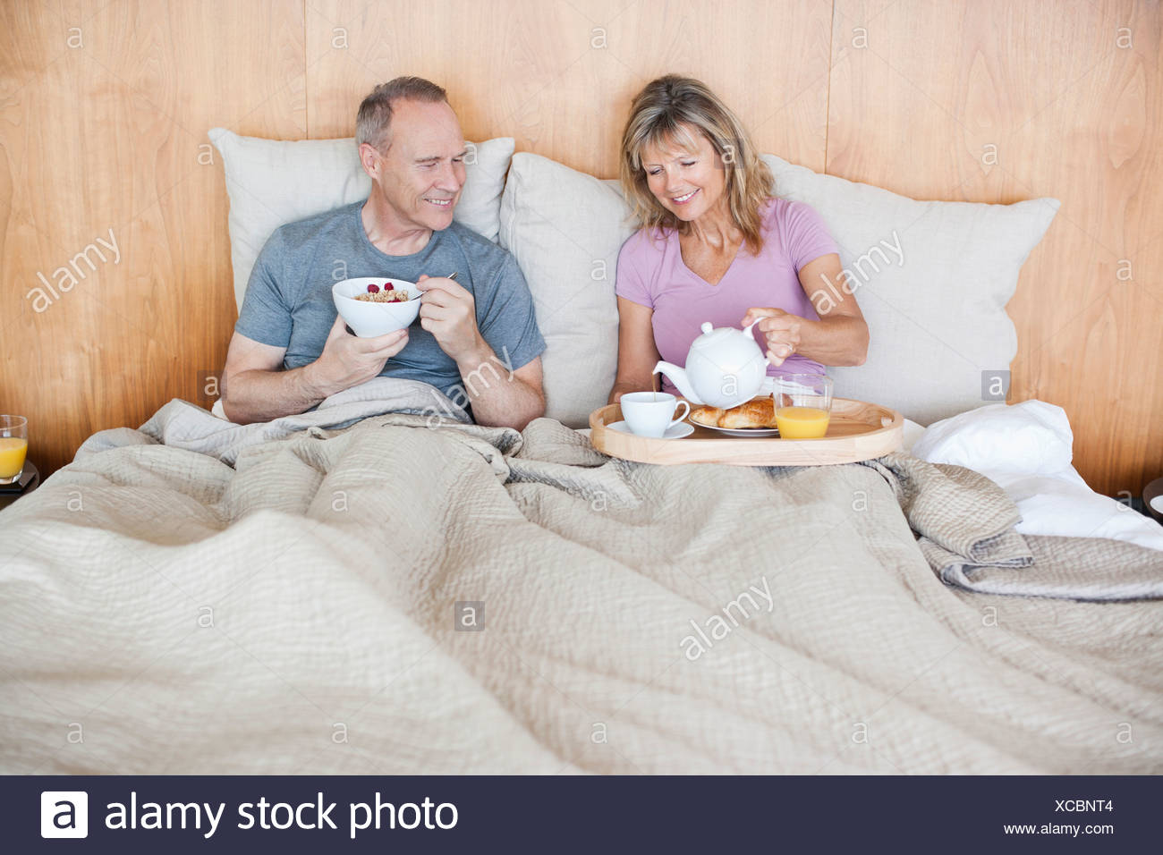Senior couple eating breakfast in bed Photo Stock
