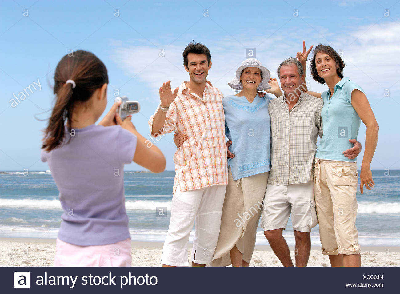 Girl 79 photographier three generation family on beach posing smiling et mer en arrière-plan Photo Stock