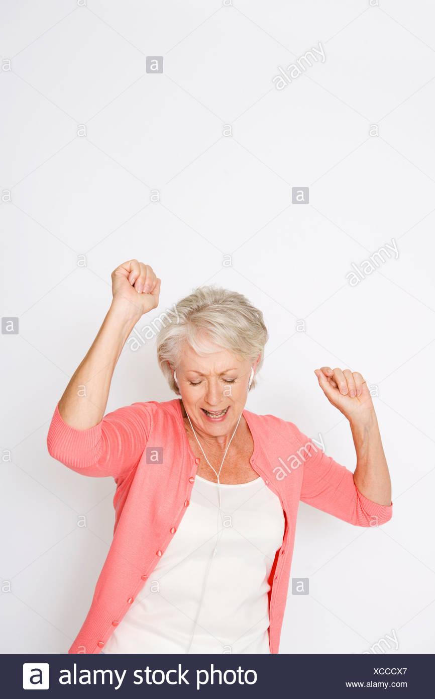 A senior woman dancing de la musique sur un lecteur mp3 Photo Stock