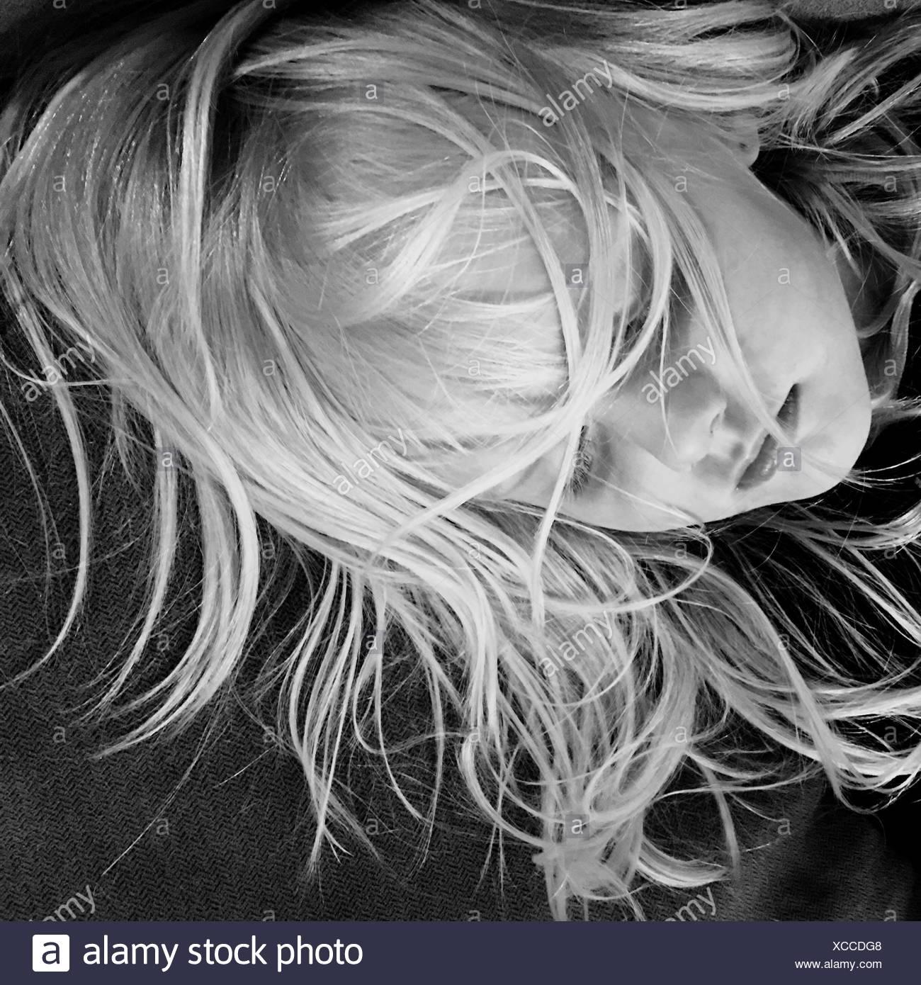 Portrait de jeune fille avec les cheveux en désordre sur le lit de couchage Photo Stock