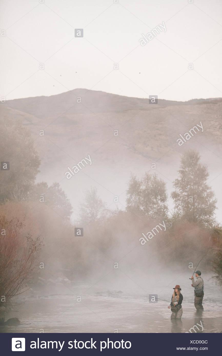 Un couple, un homme et femme debout au milieu de la pêche de mouche d'eau dans une rivière. Photo Stock