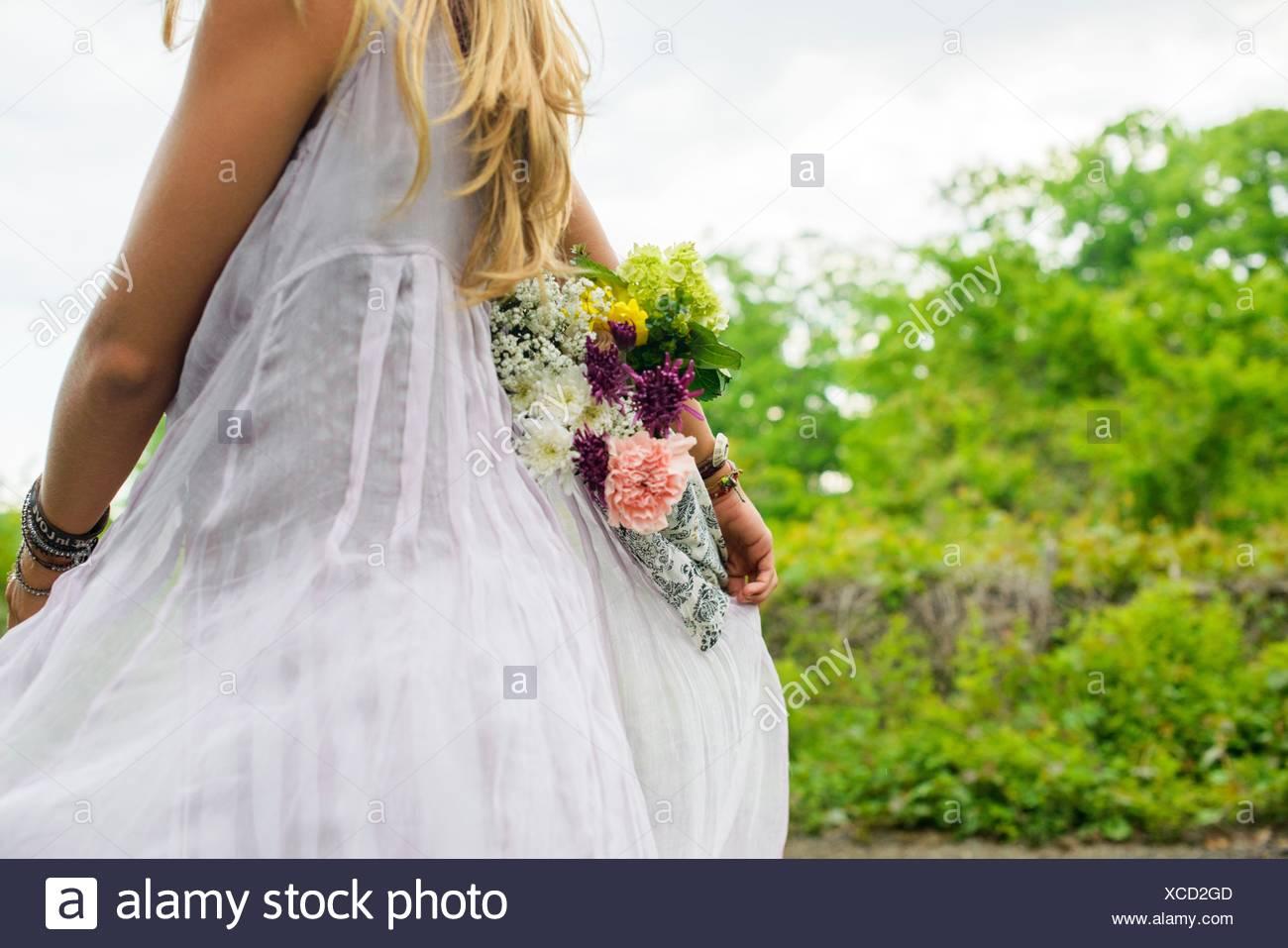 Cropped shot of young woman wearing white dress exerçant son bouquet de fleurs derrière son dos Photo Stock