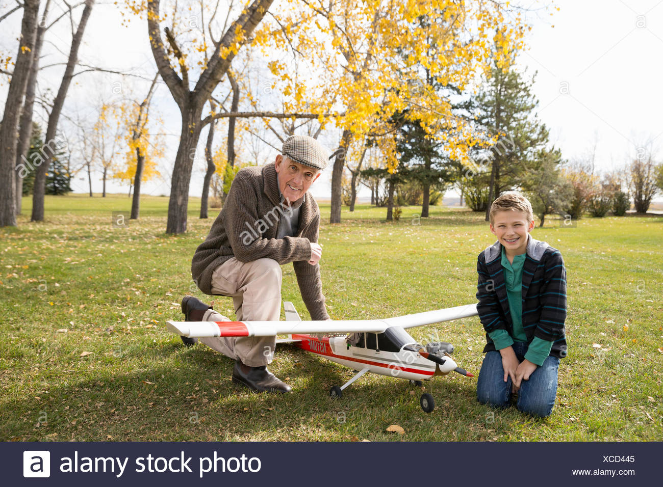 Portrait grand-père et petit-fils avec maquette avion in autumn park Photo Stock