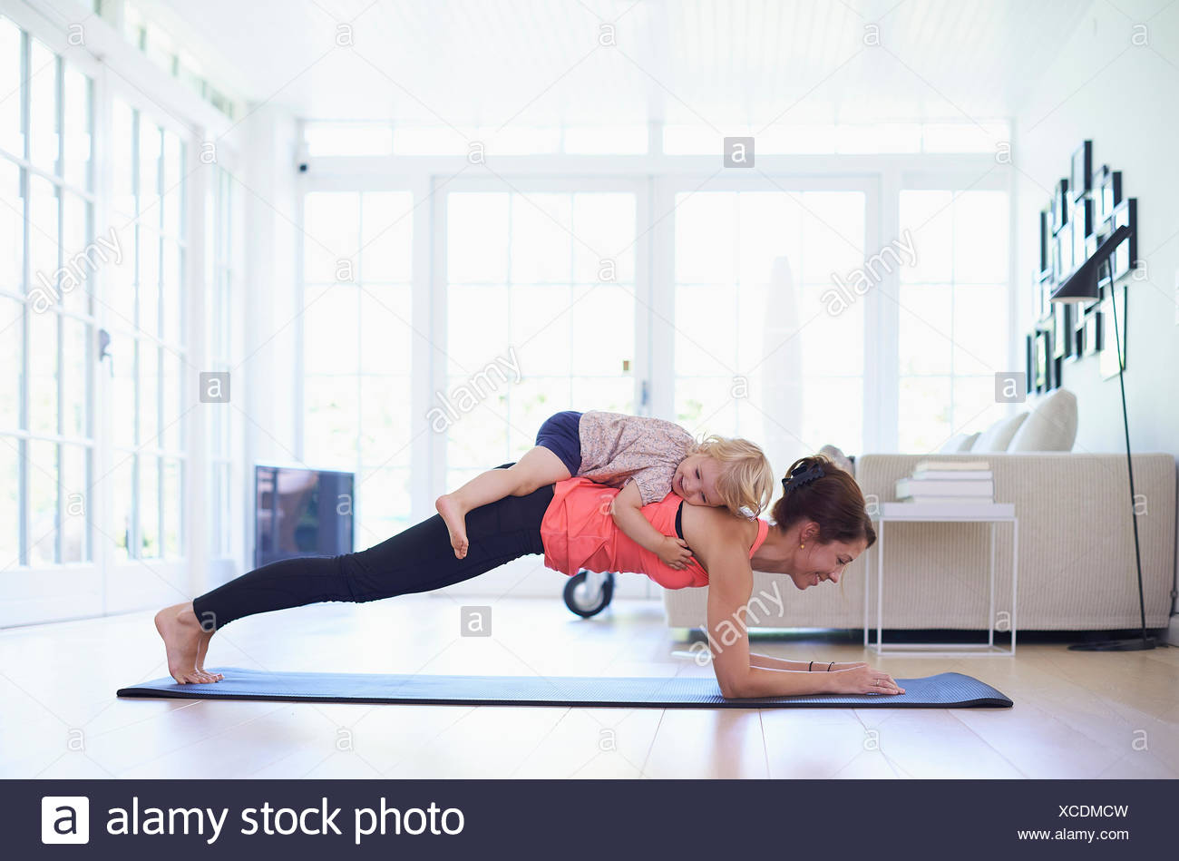 Mid adult mother pratiquant le yoga avec bébé fille sur elle Photo Stock