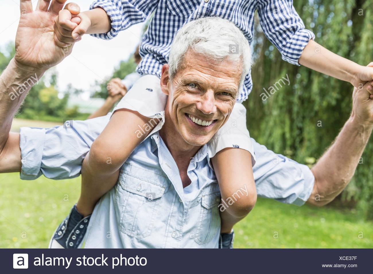Portrait de grand-père en petit-fils porter épaule donnant dans le jardin Photo Stock