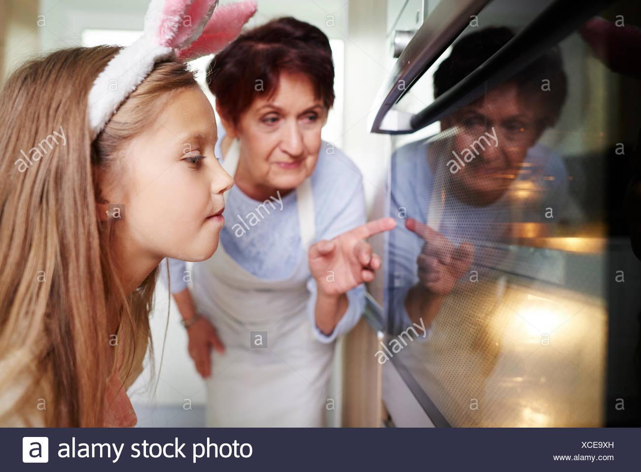 Grand-mère et fille regardant dans la cuisine four biscuits de Pâques Photo Stock