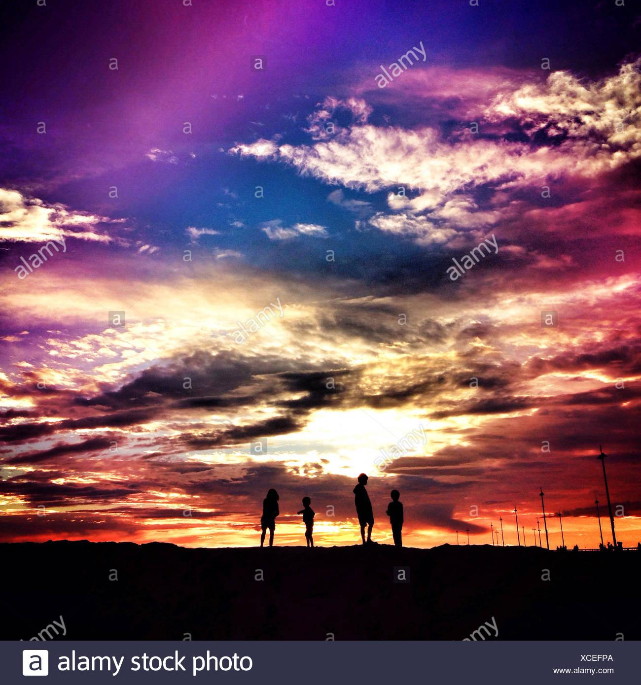 Silhouette de quatre enfants au coucher du soleil Photo Stock