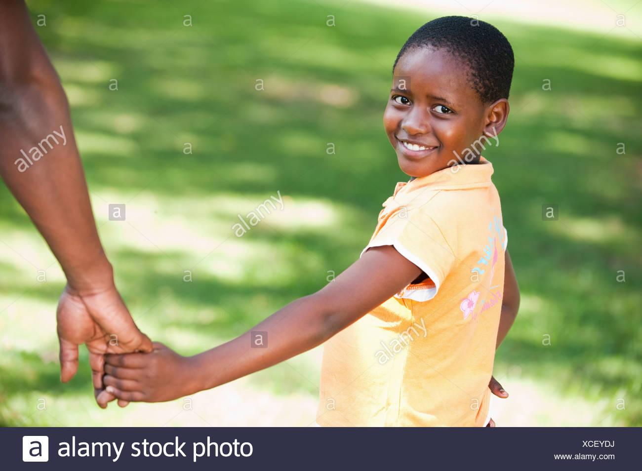 Portrait of Girl (8-9) holding pères part, Johannesburg, la Province de Gauteng, Afrique du Sud Banque D'Images