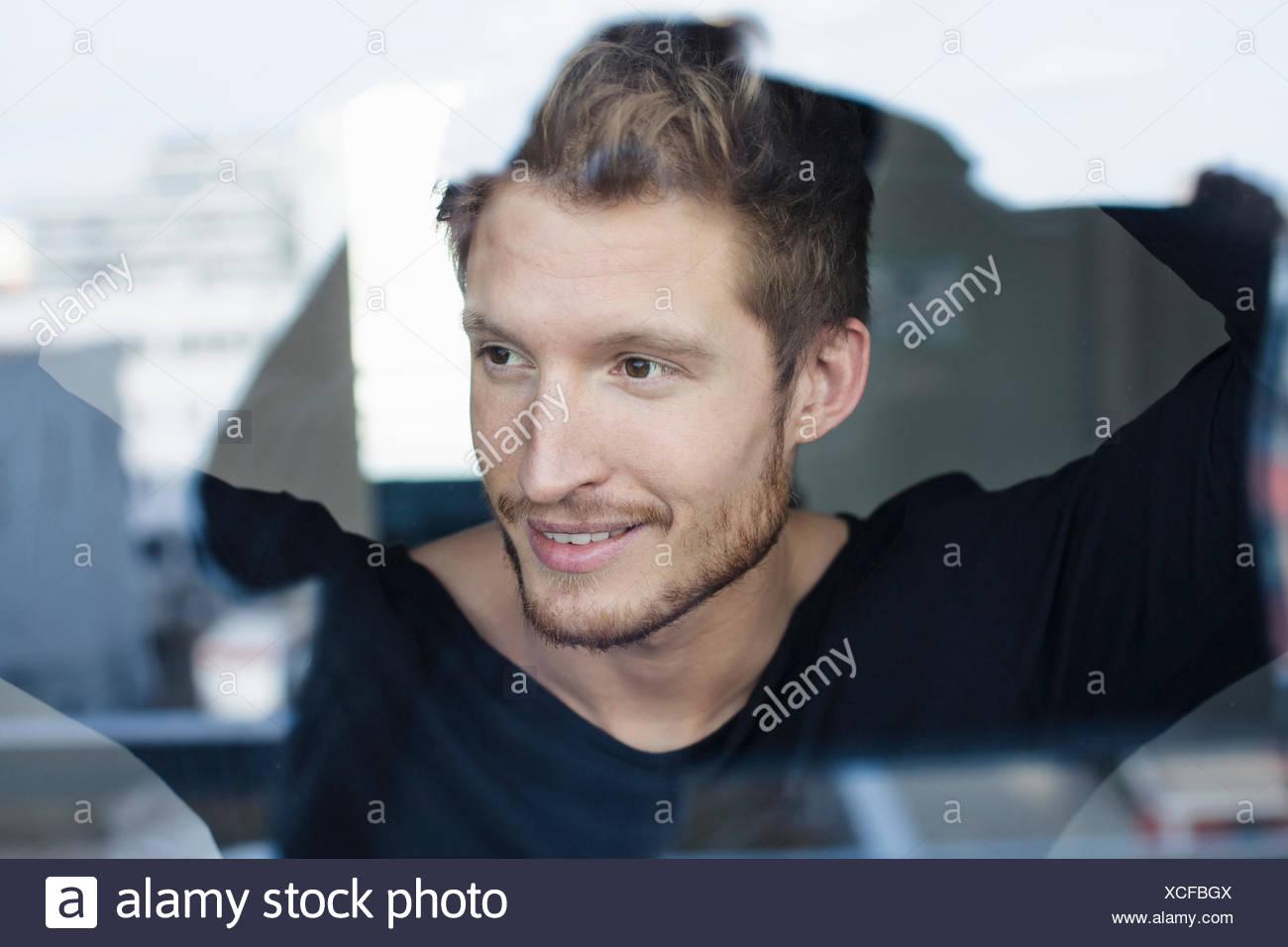 Jeune homme à la fenêtre de Photo Stock