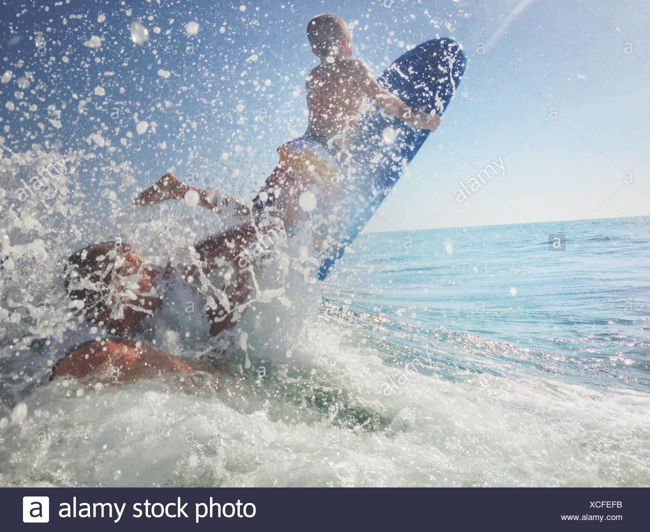 Père et fils jouant dans l'océan avec planche de surf, Californie, États-Unis Banque D'Images