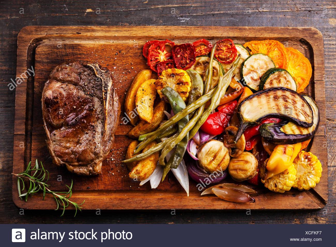 Pavé de boeuf Club et légumes grillés sur une planche à découper sur fond de bois foncé Photo Stock