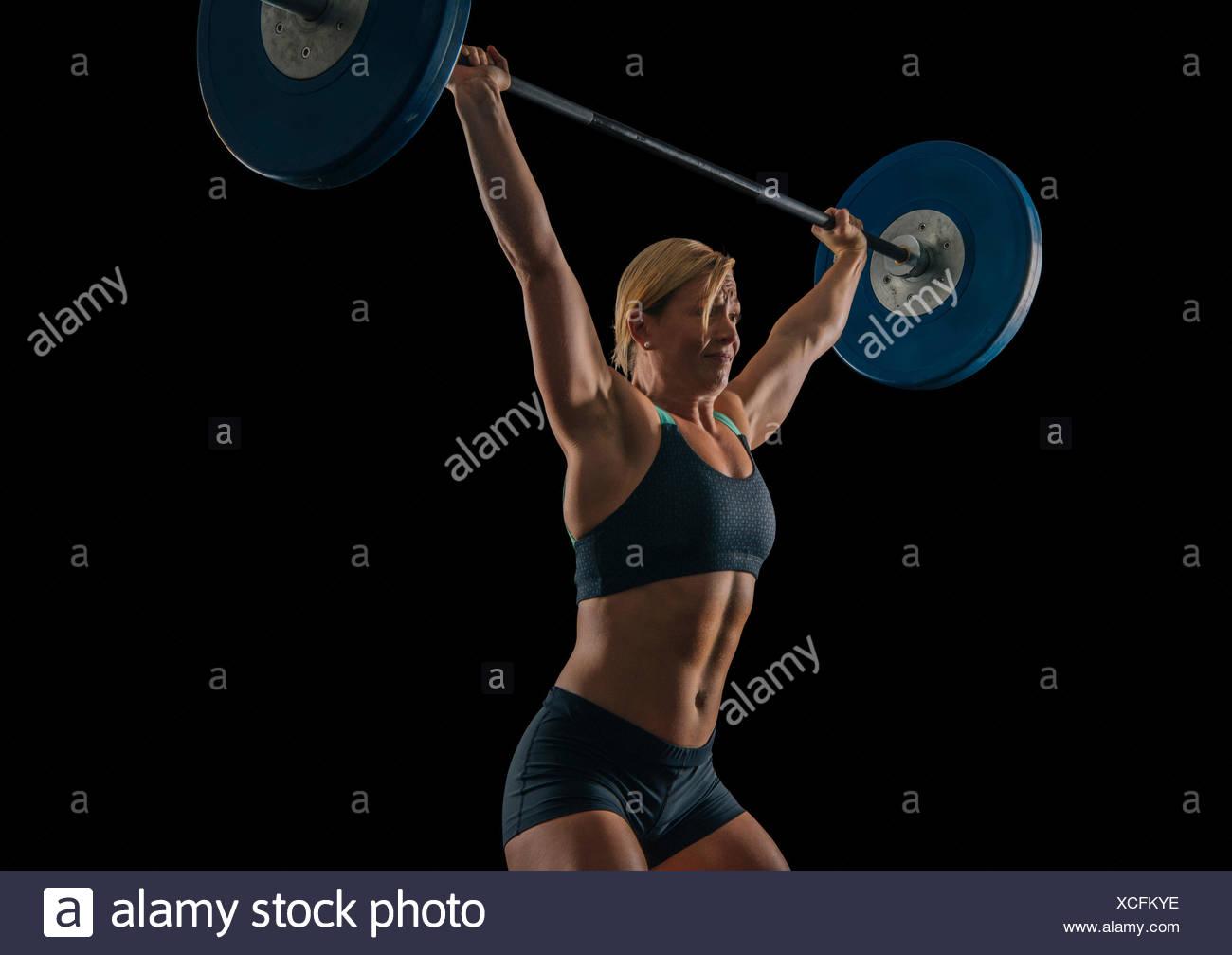 Les jeunes femmes pratiquant l'haltérophile haltérophilie barbell snatch Photo Stock