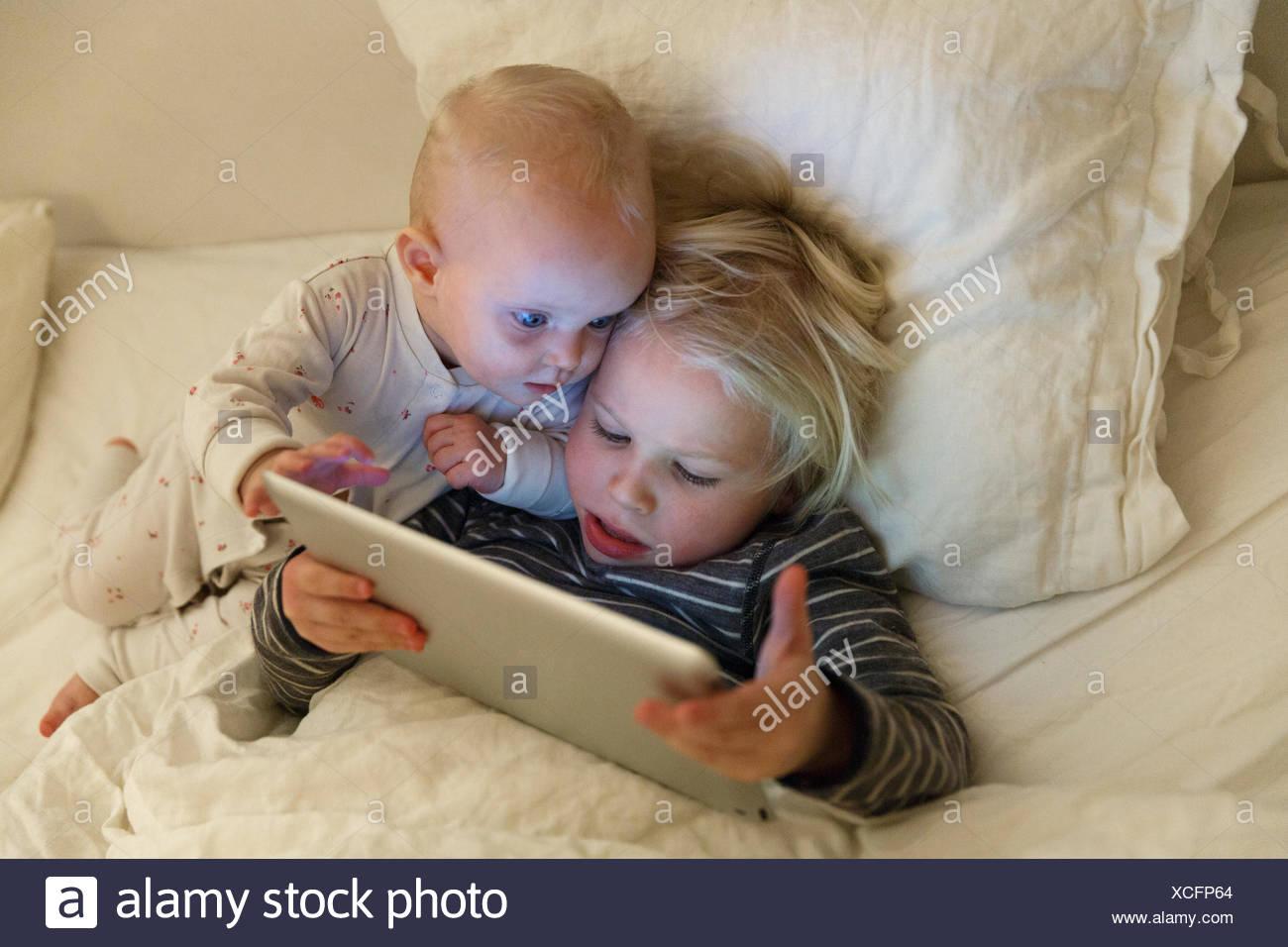 Les enfants à l'aide d'un tablet in bed Photo Stock