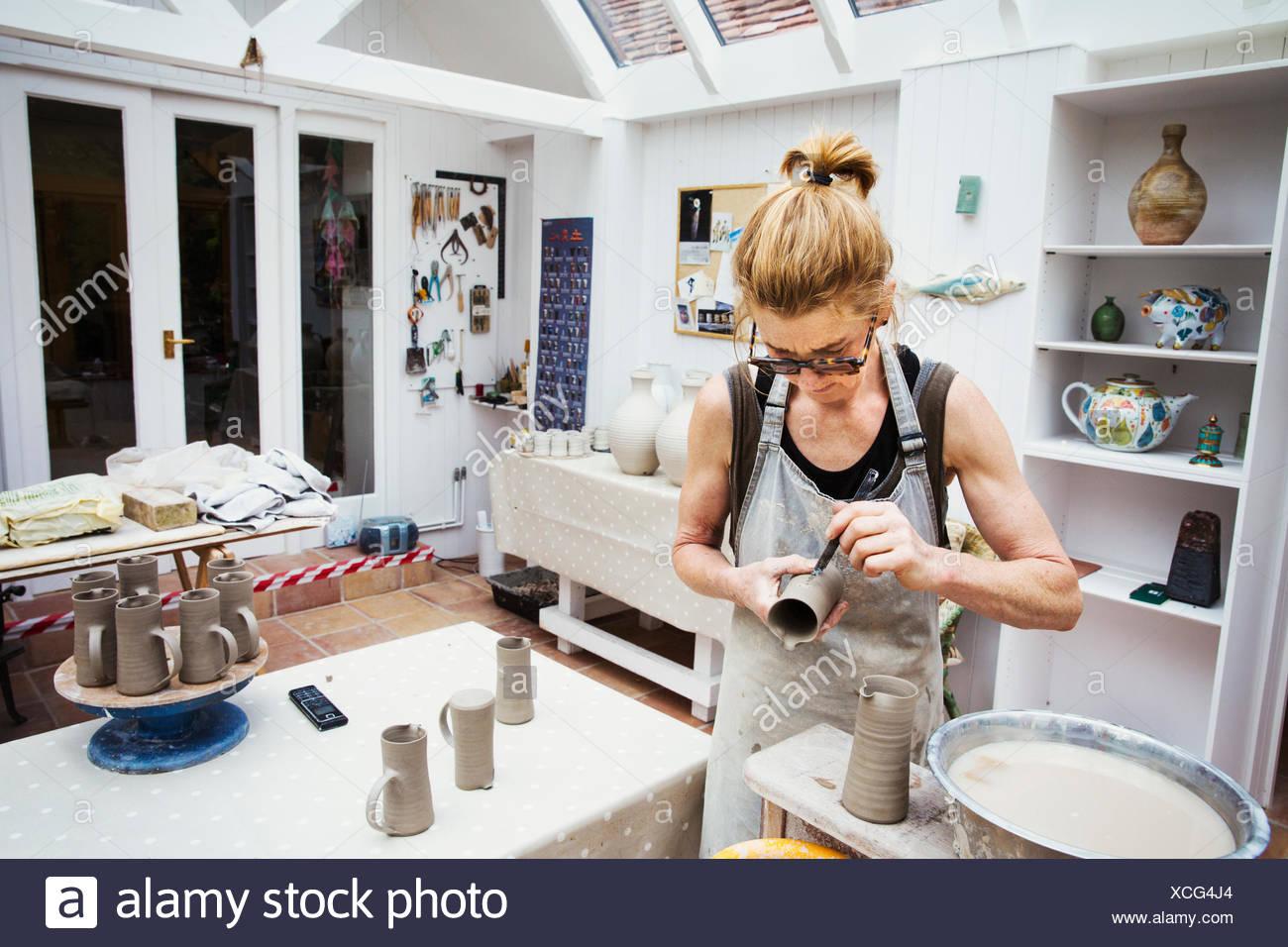 Un potter de la manipulation d'un pot d'argile humide, en lissant les bords et la préparer pour la cuisson au four. Banque D'Images
