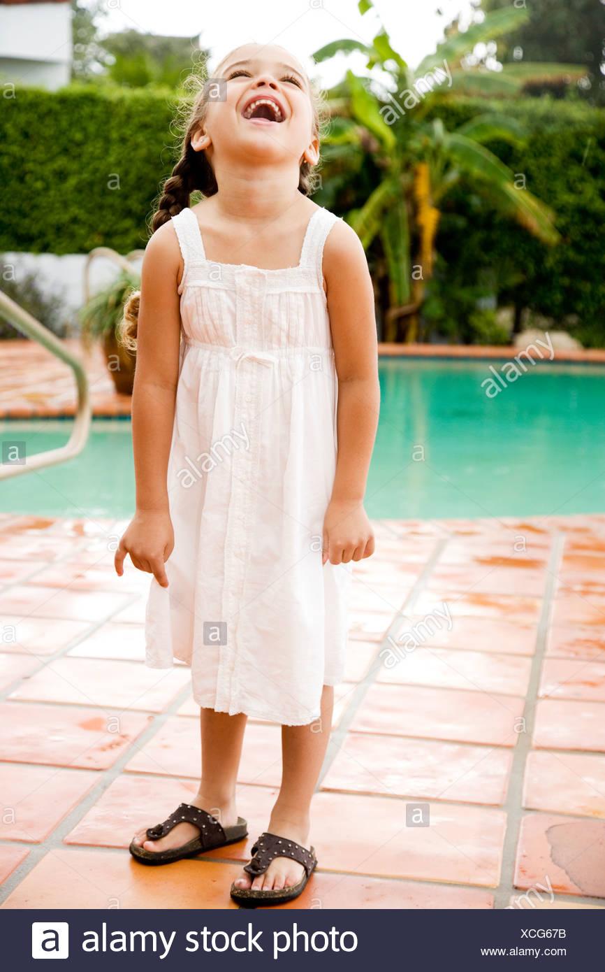 Young Hispanic Girl standing et de rire par un pool Photo Stock
