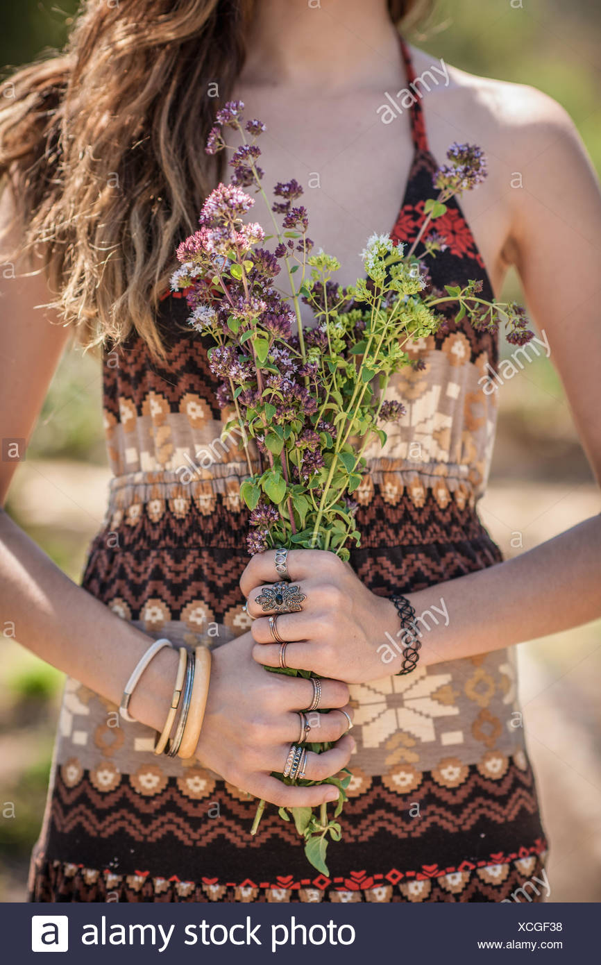 Cropped shot of young woman holding bunch of wildflowers Photo Stock