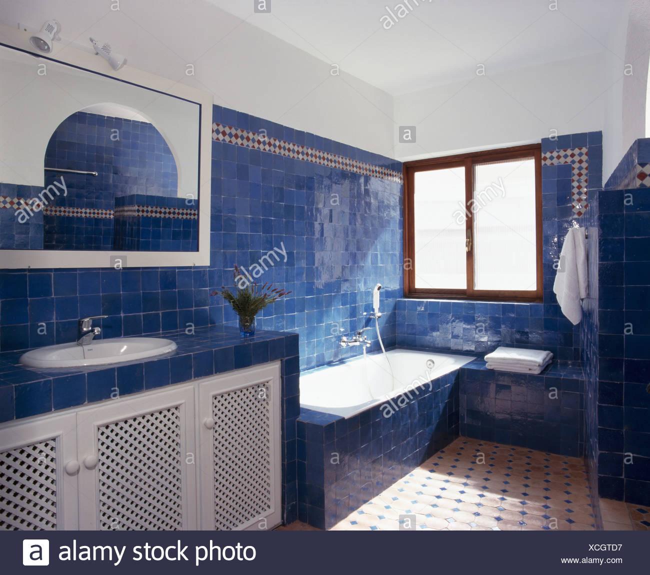 Carreaux bleu vif sur le mur au-dessus de baignoire dans la ...