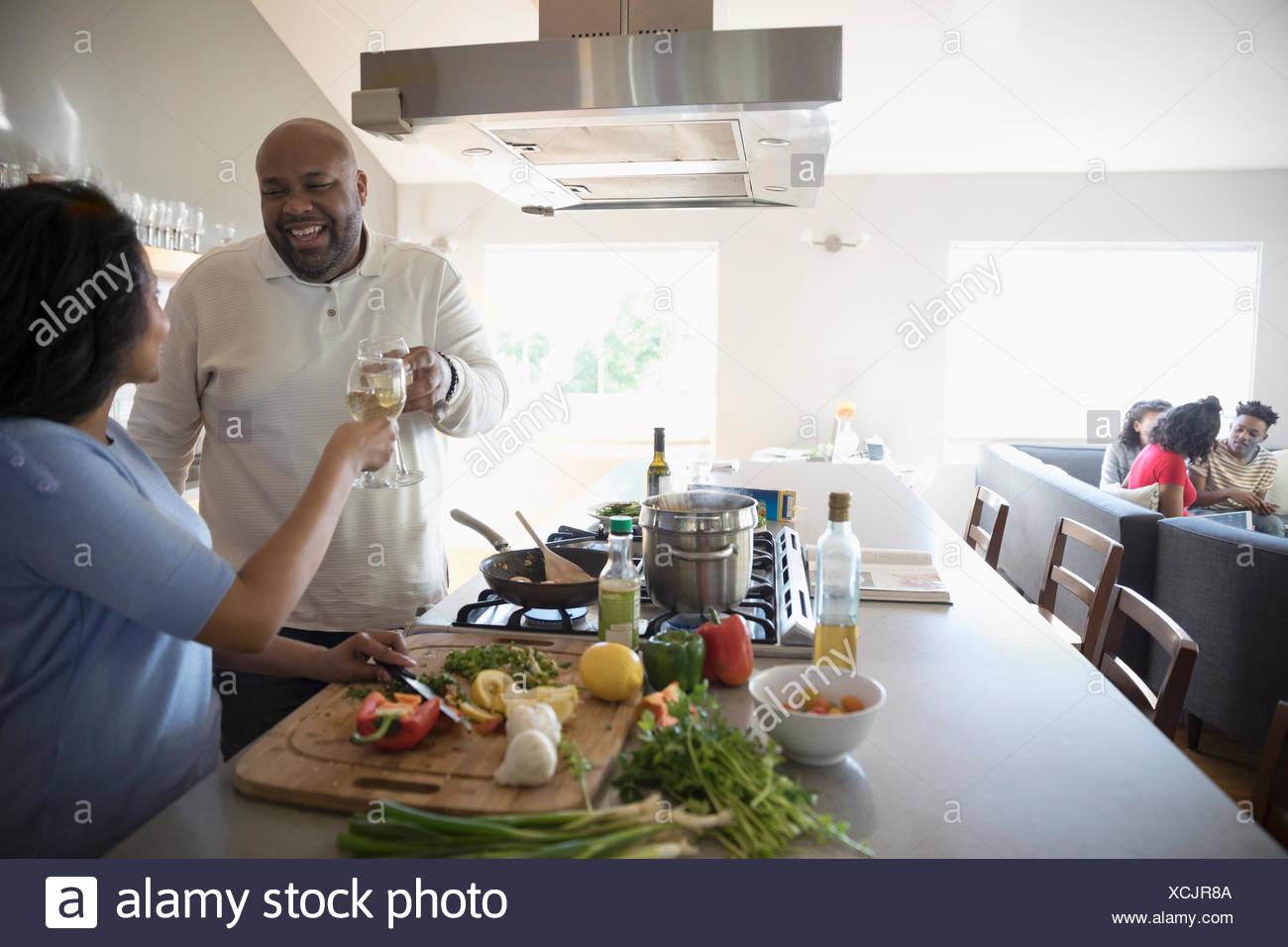 African American couple cooking et boire le vin blanc dans la cuisine Photo Stock