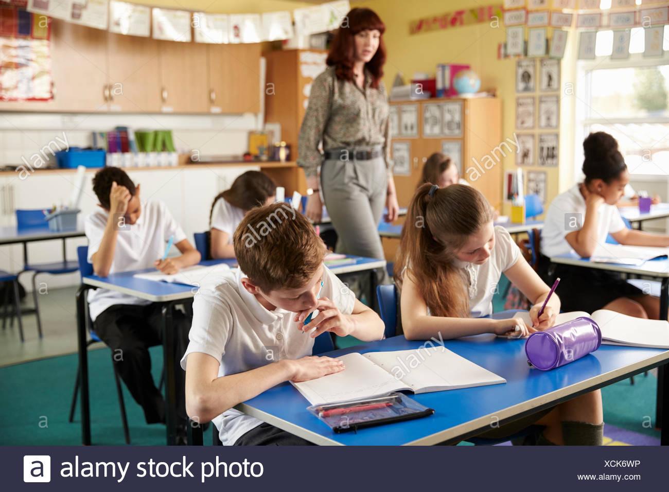 La marche de l'enseignant dans sa classe de l'école primaire d'occupation Photo Stock