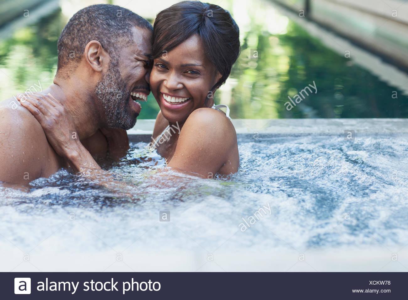 Le partage d'un couple rire dans un bain à remous Photo Stock