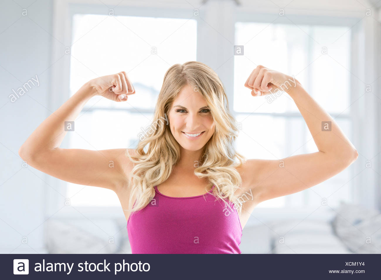 Smiling blonde woman flexing muscles Photo Stock