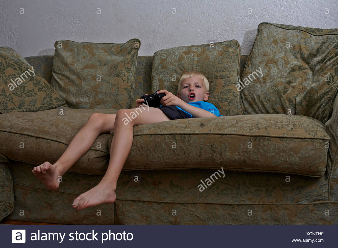 Boy playing video game in living room Banque D'Images