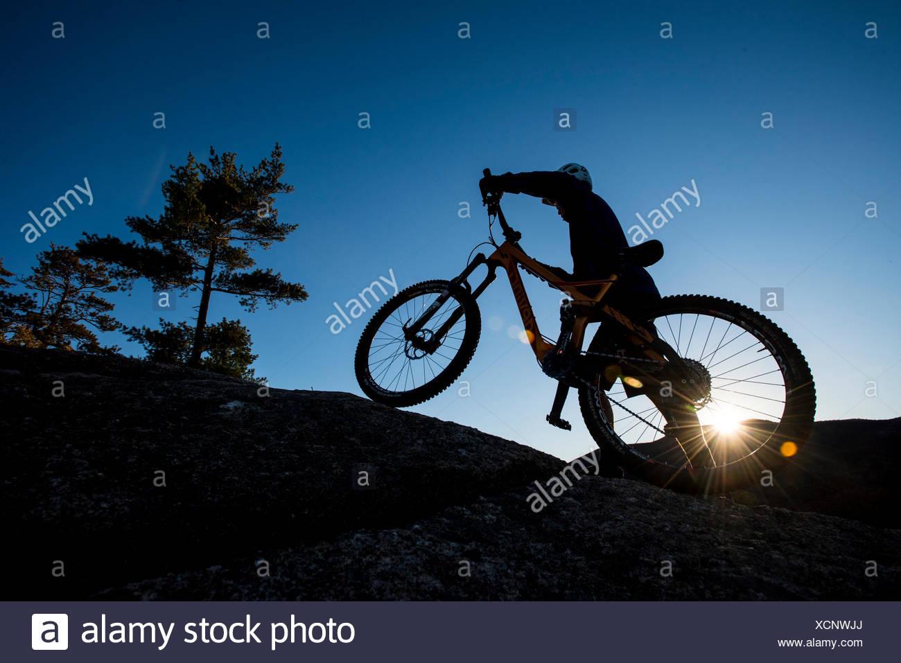 Silhouette d'Alex Leich avec VTT sur les Minimums de granit dans la région de North Conway, New Hampshire Photo Stock