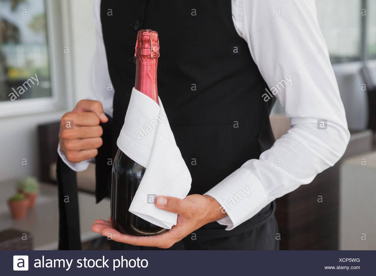 Bien habillé waiter holding magnum de champagne Photo Stock