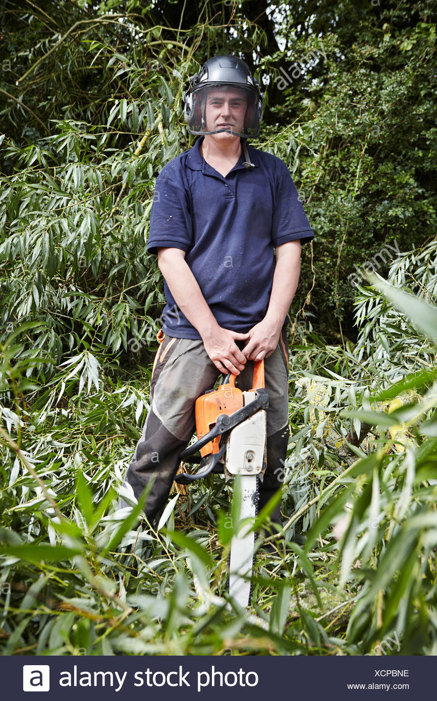Worker holding chainsaw en forêt Photo Stock