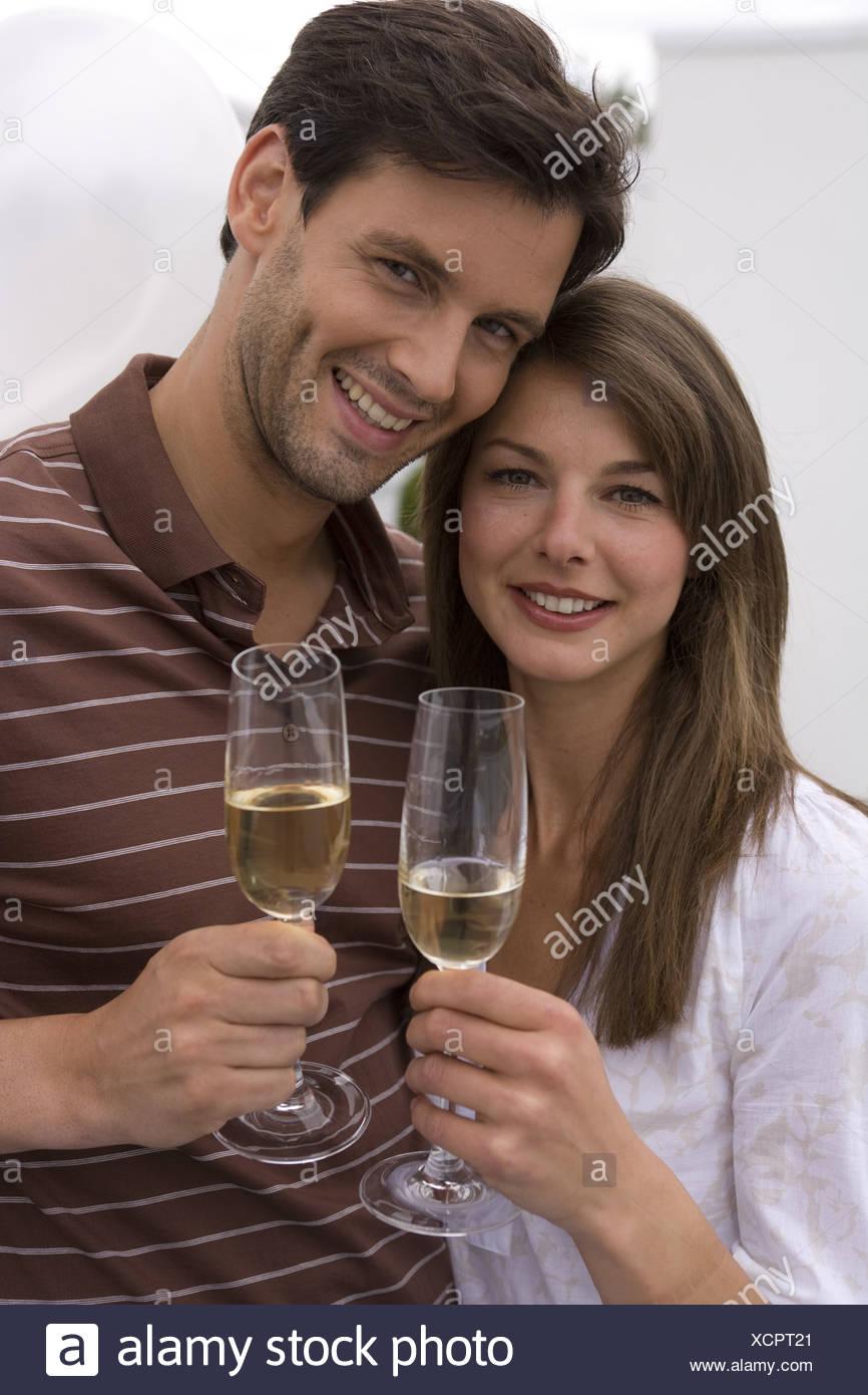 Mate smiling amoureusement verres de champagne champagne-verres célèbre portrait à l'extérieur de 20 à 30 ans 30 à 40 ans se cogner Photo Stock