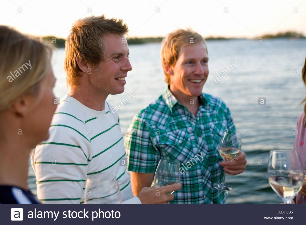 Trois personnes rire et boire, Fejan, archipel de Stockholm, Suède. Banque D'Images