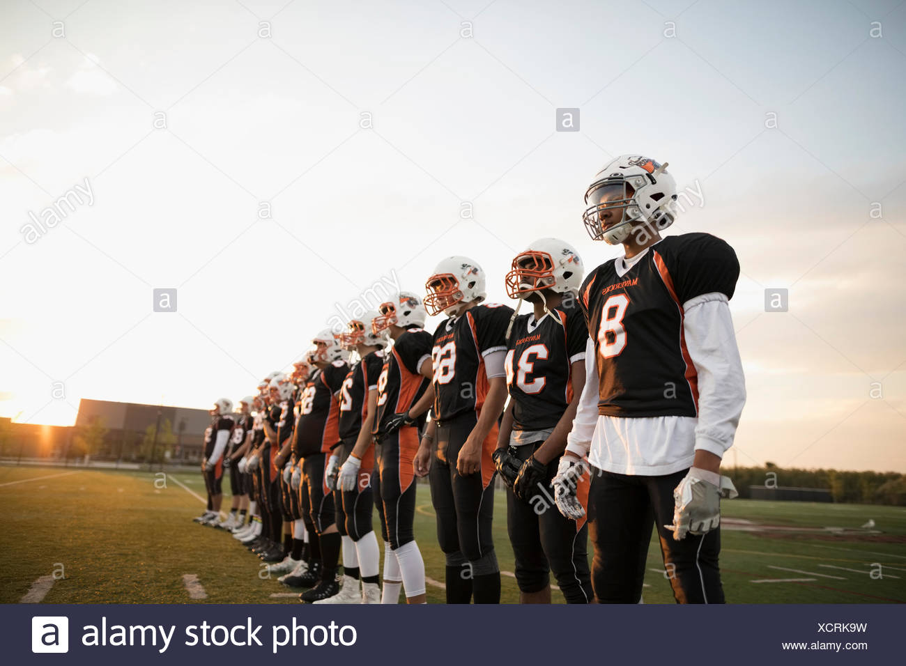 Teenage boy high school football team standing in a row sur terrain de football Photo Stock