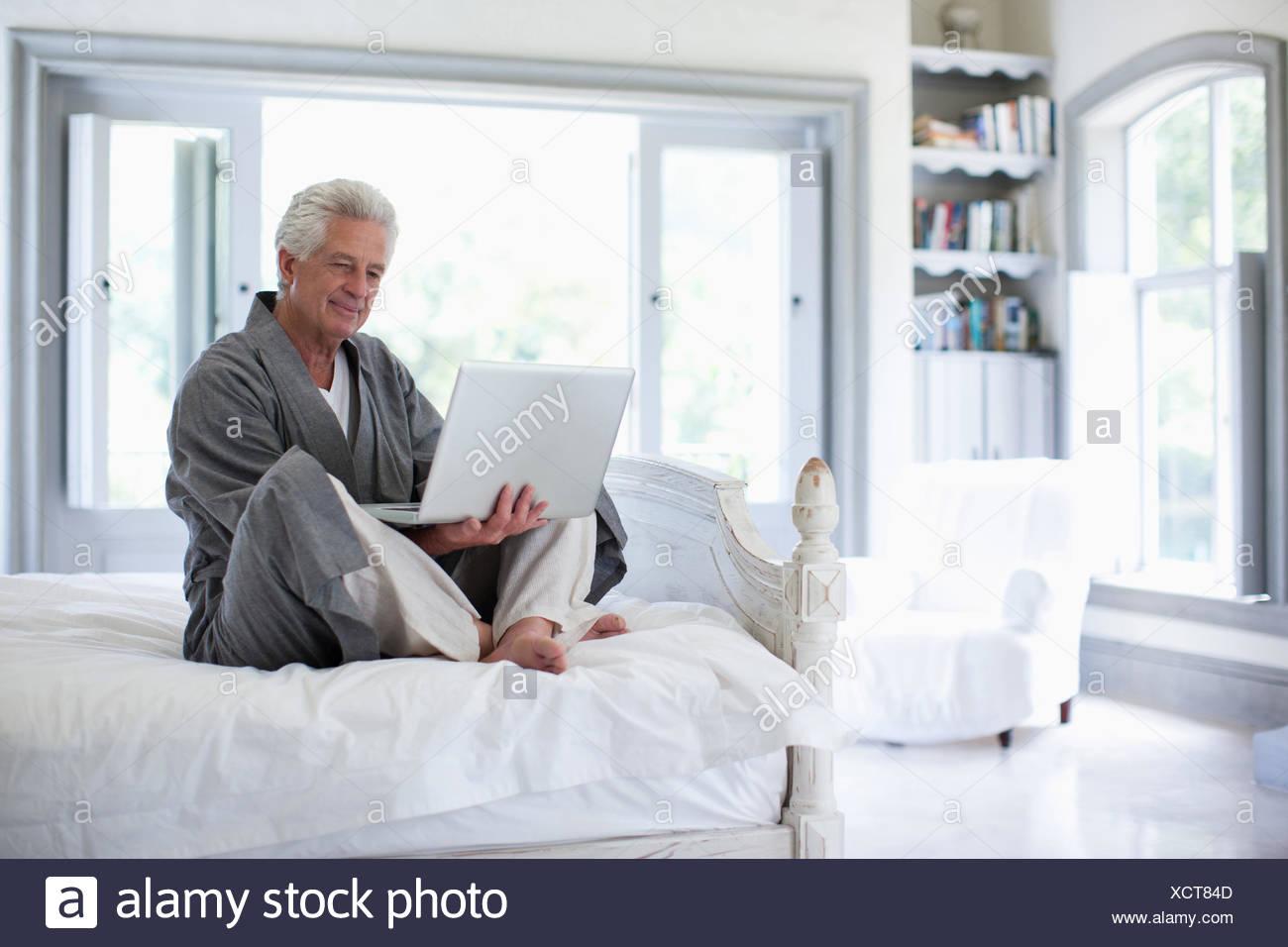 Man en peignoir à l'aide d'un coffre dans la chambre Photo Stock