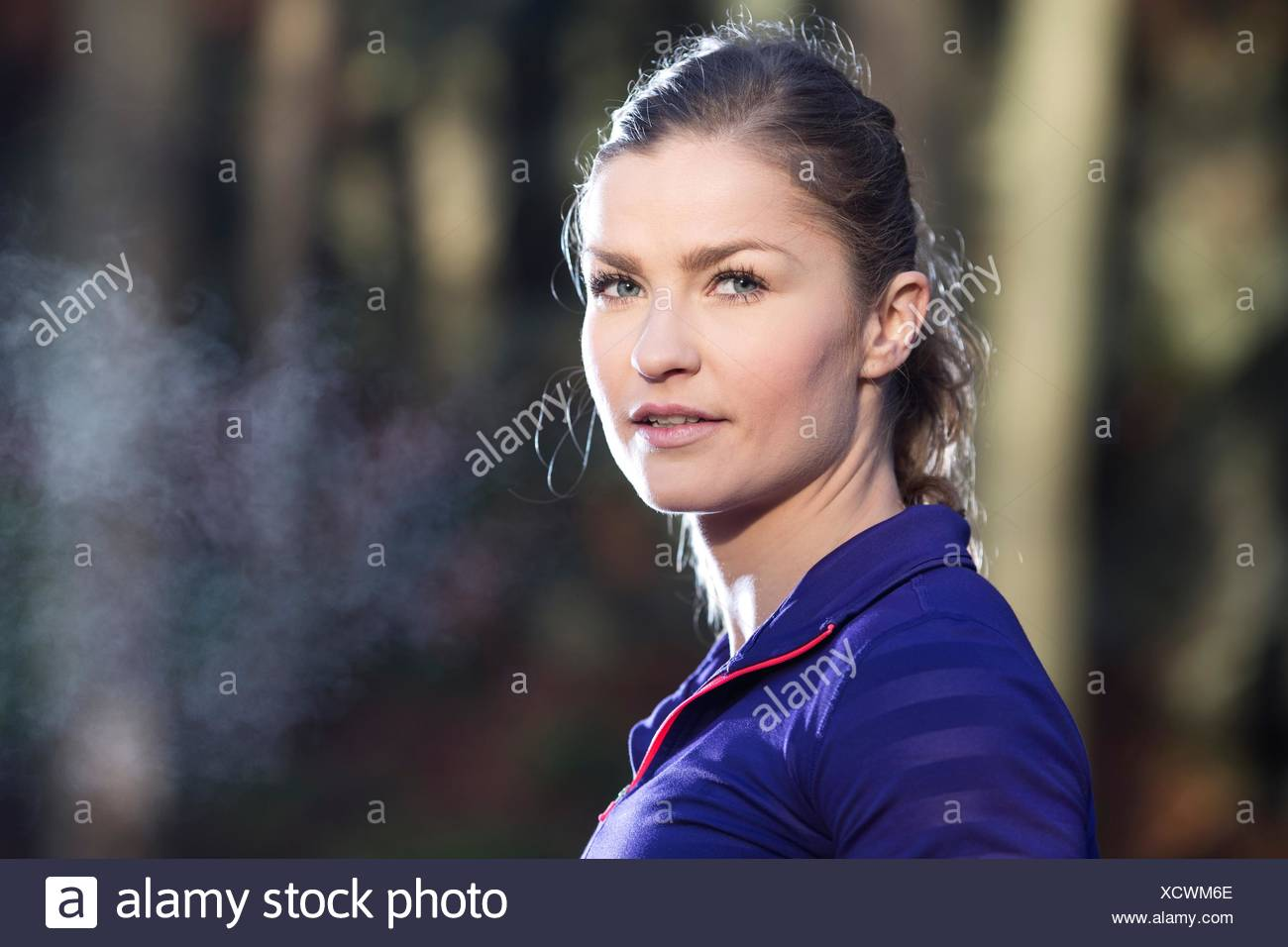 Portrait of young woman looking at camera, condensation de souffle Photo Stock