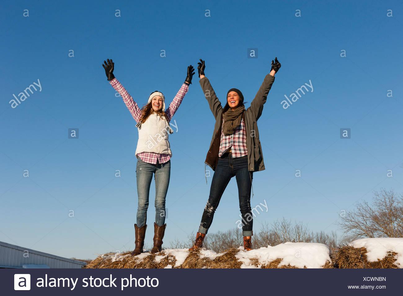Deux jeunes femmes aux bras levés sur la colline d'hiver Photo Stock